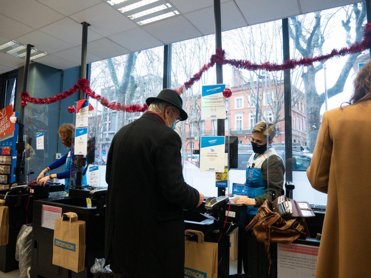 Un homme âgé passe à la caisse d'une grande enseigne pendant les courses de Noël. Toulouse, le 21 décembre 2020.