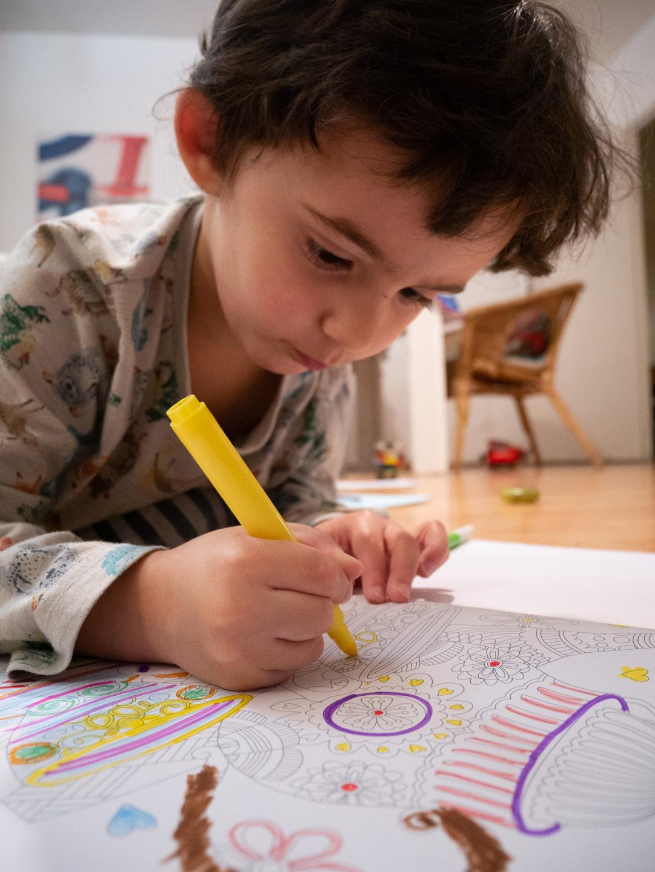 Un enfant en pyjama fait du coloriage. Alors que se profile le spectre de possibles restrictions sanitaires, les vacances de Noël ont été l'occasion pour les parents d'enfants en bas âge d'expérimenter le confinement en famille. Toulouse, décembre 2020.