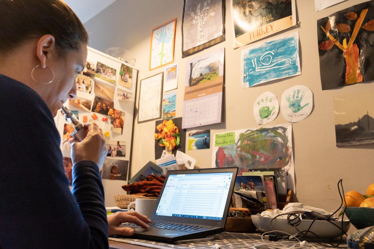 Une formatrice en langue anglaise tire une dernière fois sur sa vapoteuse. Elle s'apprête à donner un cours à distance pendant le confinement depuis la cuisine de son appartement. Sur le mur en face d'elle, des dessins de ses enfants. Toulouse, 25 novembre 2020.