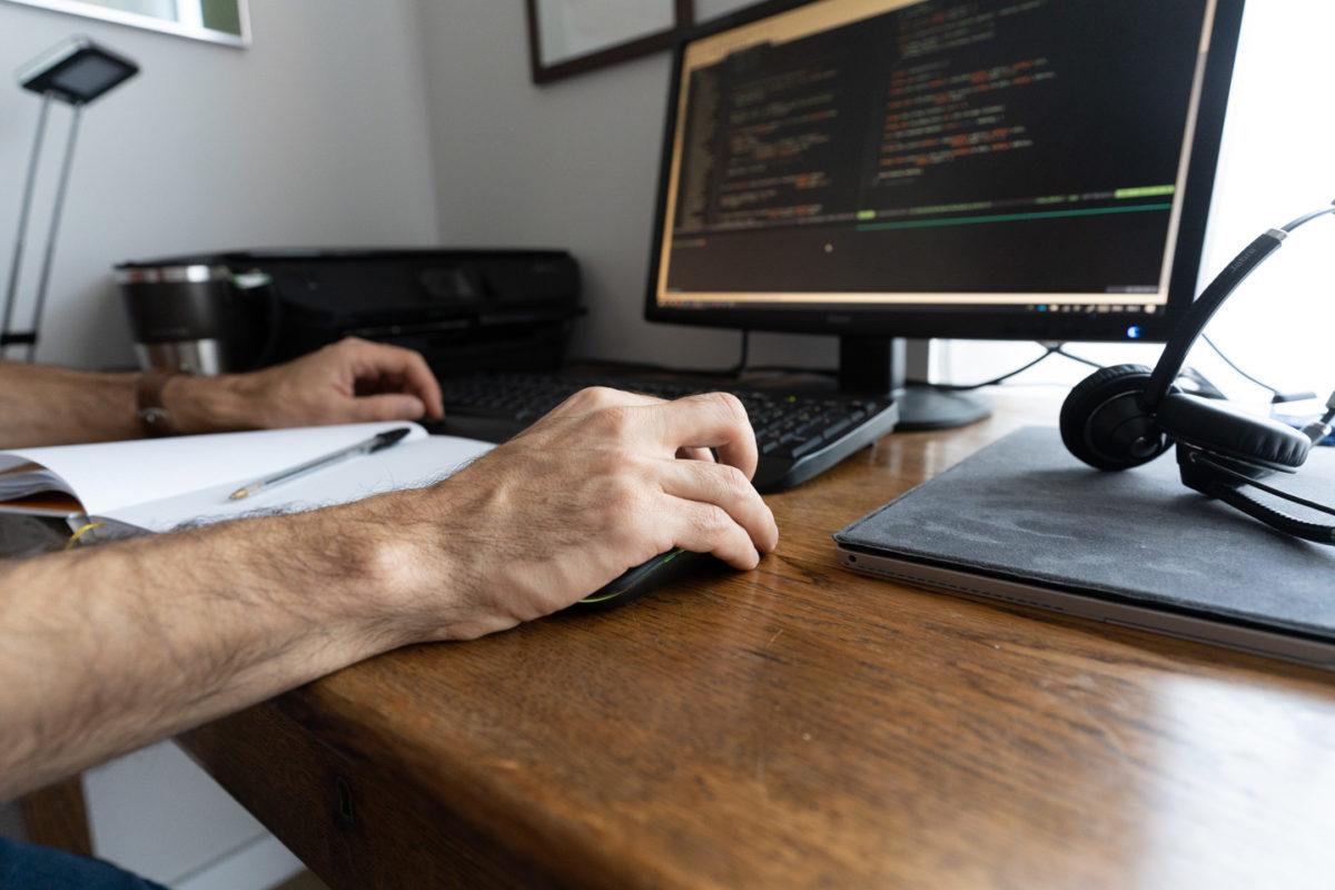 Poste de travail - avec écran, clavier, casque et cahier - d'un informaticien chez lui en télétravail. Sa main droite est posée sur la souris.
