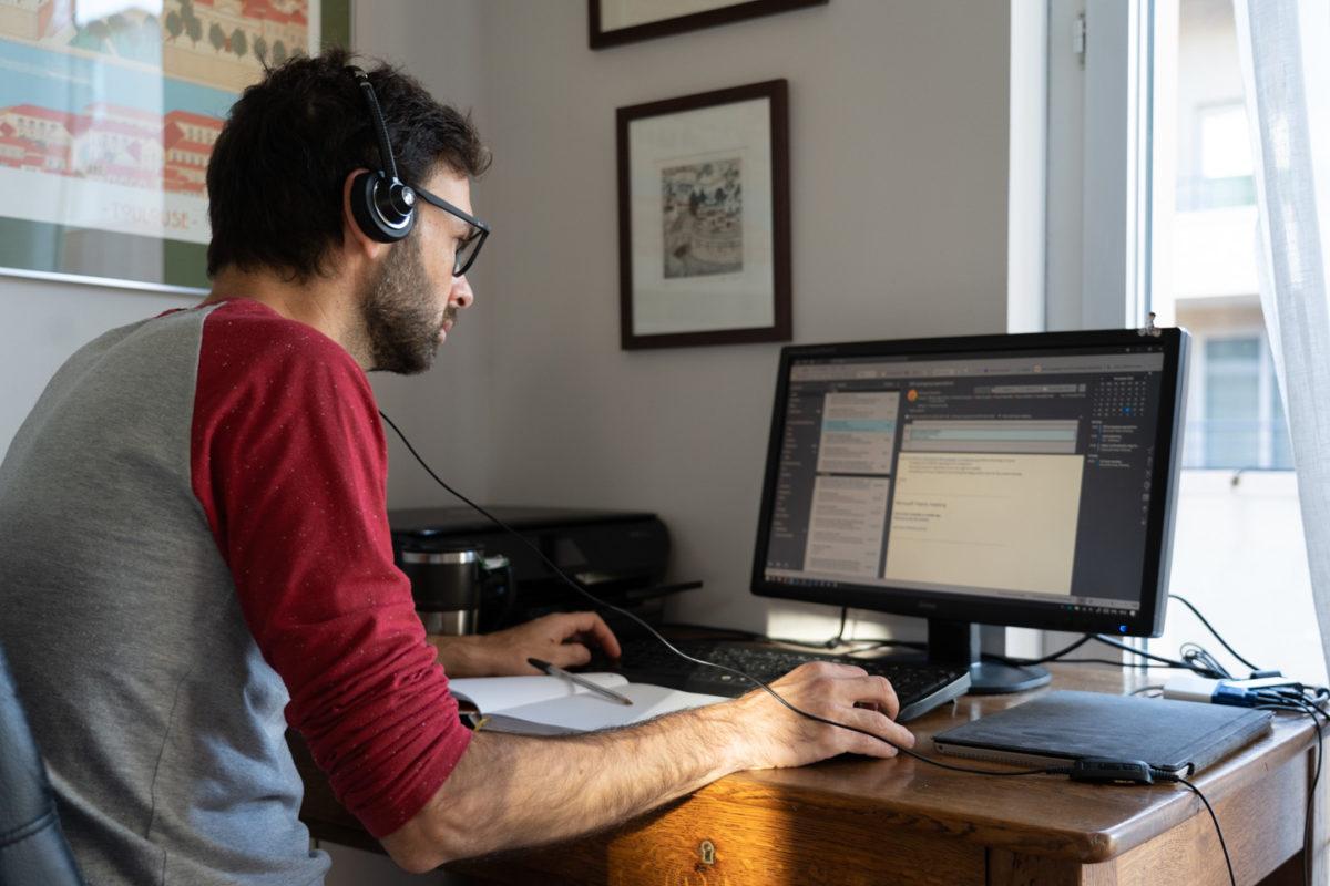 Un informaticien employé d'une start-up chez lui en télétravail devant son poste de travail. Toulouse, 26 novembre 2020.