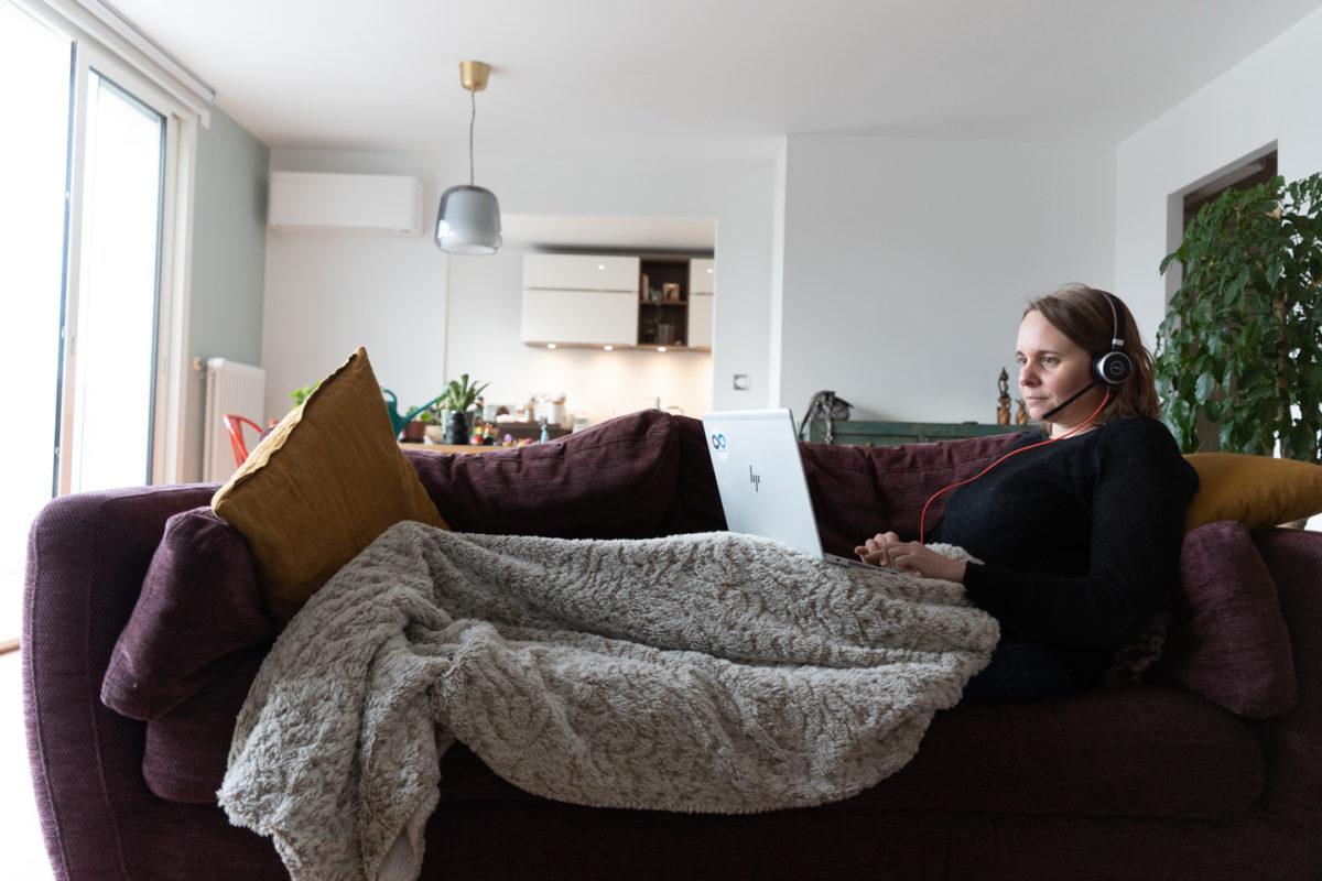 Une employée d'un grand groupe aéronautique en télétravail sur le canapé de son séjour. Toulouse, 26 novembre 2020.