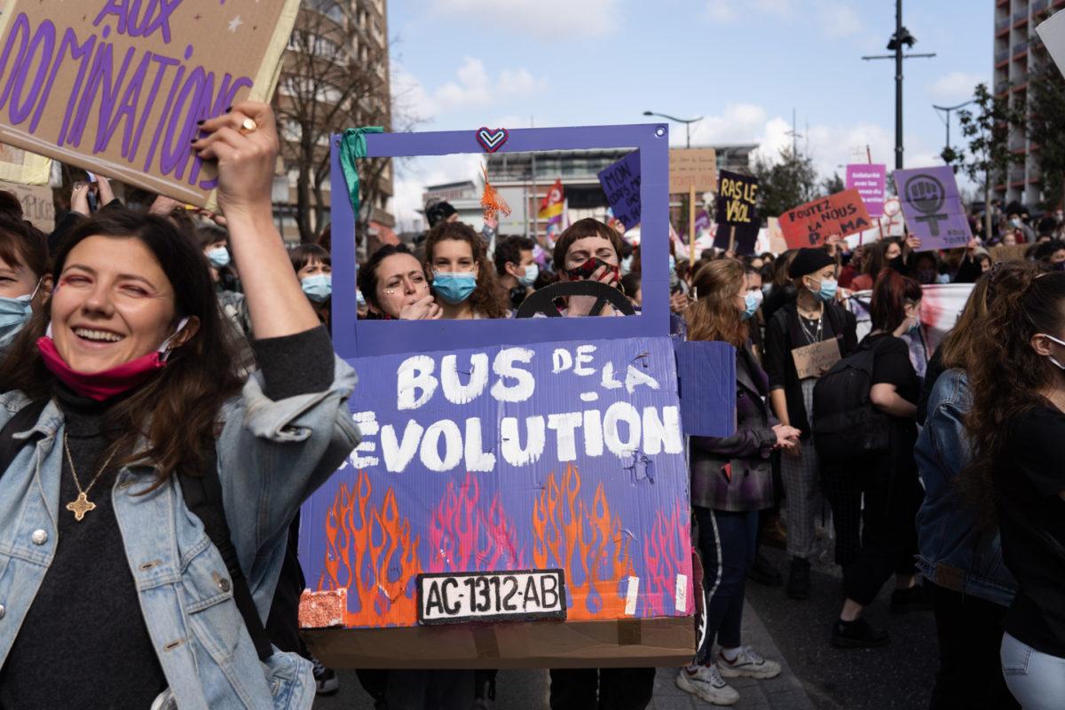 """Des manifestantes marchent derrière une pancarte à fenêtre sur laquelle on peut lire """"Le bus de la révolution"""" lors de la manifestation pour la journée sur les droits des femmes. Toulouse, 8 mars 2021."""