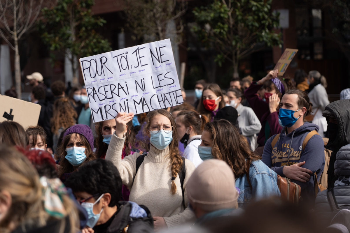 """Une manifestante montre une pancarte sur laquelle on peut lire """"Pour toi, je ne raserai ni les murs, ni ma chatte"""" lors de la manifestation pour la journée sur les droits des femmes. Toulouse, 8 mars 2021."""