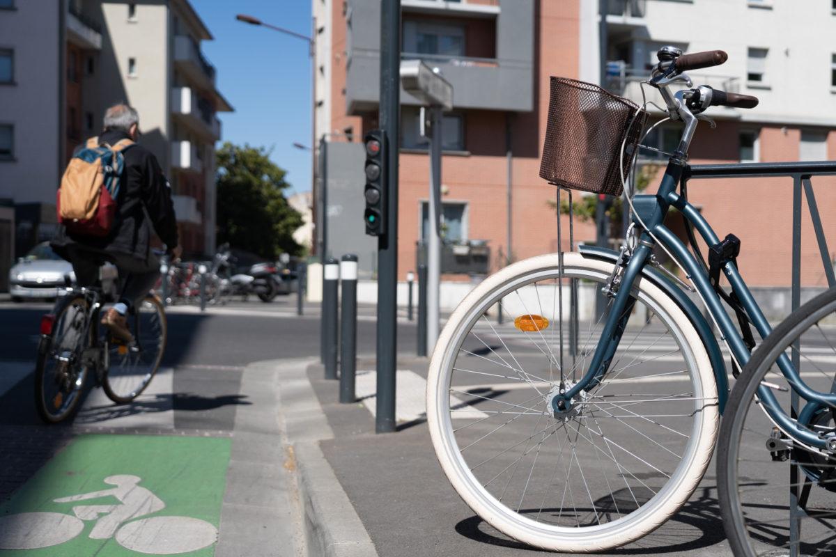Un vélo de ville est garé à côté du piste cyclable à Toulouse tandis qu'un cycliste s'apprête à prendre un carrefour. Toulouse, le 23 avril 2021.