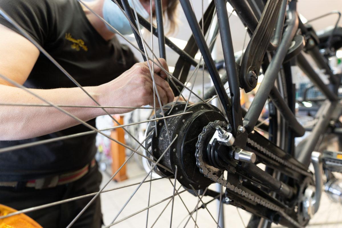 Une employé de la boutique de réparation de vélo Mécanicycle travaille sur la roue arrière d'un vélo. Toulouse, le 23 avril 2021.