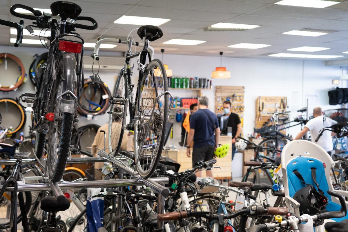 Vue sur l'intérieur d'une boutique de réparations de vélos. En premier plan, des vélos. En arrière plan, des clients.