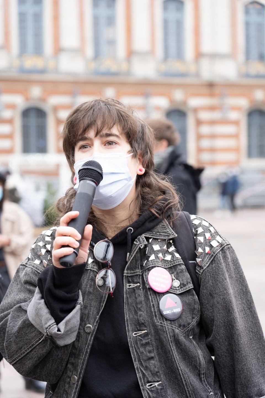 """Louise Lourdon prend le micro pour dénoncer la politique sanitaire du gouvernement pendant la crise du Covid à l'occasion du rassemblement organisé par ActUp Sud-Ouest pour la journée mondiale contre le VIH/SIDA. Condamnée en première instance le 26 novembre 2019 à 300€ d'amende avec sursis """"pour infjures publiques"""" suite à une plainte de la Manif Pour Tous concernant une contre-manifestation ayant eu lieu en 2017, elle a fait appel. Le tribunal de grande instance de Toulouse rendra son jugement le 8 décembre. Toulouse, le 1er décembre 2020."""