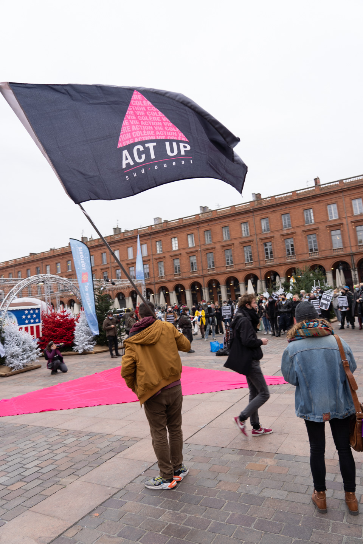 Un militant brandit le drapeau Act Up sur la place du Capitole à l'occasion du rassemblement organisé par ActUp Sud-Ouest pour la journée mondiale contre le VIH/SIDA. Toulouse, le 1er décembre 2020.