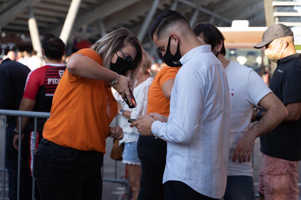 Une hôtesse d'accueil vérifier l'abonnement d'un membre du public.  Près de 19000 contrôles de pass sanitaire ont été effectués dimanche soir au stade Ernest Wallon à l'occasion de la rencontre entre le Stade Toulousain et le Rugby Club Toulonnais, qui s'est jouée à guichet fermé. Après une année de matches à huis-clos en raison de la crise sanitaire, le public s'est rendu en masse au stade à l'occasion du match de clôture de la 2e journée du Top 14, que le Stade Toulousain a remporté 41 à 10. Toulouse, stade Ernest Wallon, le 12 septembre 2021.
