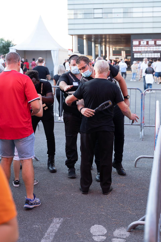 """Un agent de sécurité passe un membre du public au détecteur de métaux (la """"raquette""""). Après une année de matches à huis-clos en raison de la crise sanitaire, le public a pu de nouveau se rendre au stade Ernest Wallon à l'occasion du match de clôture de la 2e journée du Top 14. Champion de France en titre, le Stade Toulousain recevait le Rugby Club Toulonnais. Le match s'est joué à guichets fermés et près de 19000 contrôles de pass sanitaires ont été effectués à l'entrée du stade. Le Stade Toulousain l'a remporté par 41 à 10. Toulouse, stade Ernest Wallon, le 12 septembre 2021."""