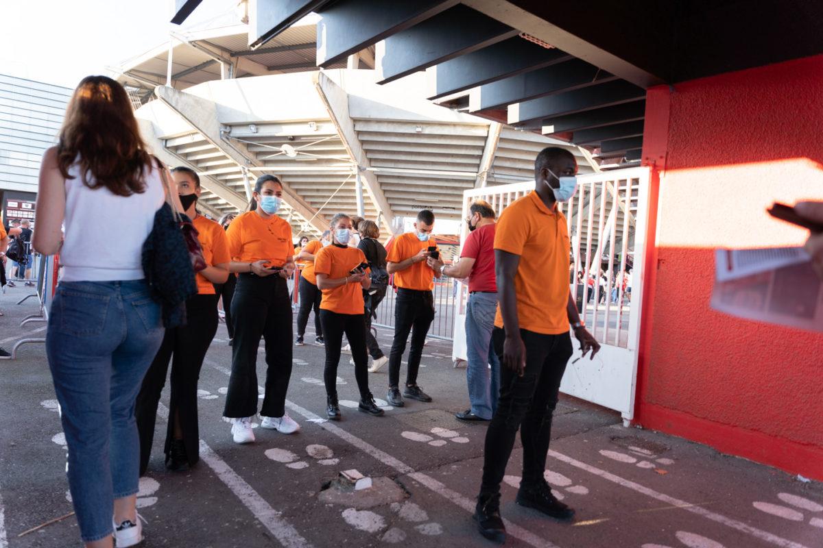Des employés d'accueil attendent le public à l'entrée du stade. Après une année de matches à huis-clos en raison de la crise sanitaire, le public a pu de nouveau se rendre au stade Ernest Wallon à l'occasion du match de clôture de la 2e journée du Top 14. Champion de France en titre, le Stade Toulousain recevait le Rugby Club Toulonnais. Le match s'est joué à guichets fermés et près de 19000 contrôles de pass sanitaires ont été effectués à l'entrée du stade. Le Stade Toulousain l'a remporté par 41 à 10. Toulouse, stade Ernest Wallon, le 12 septembre 2021.