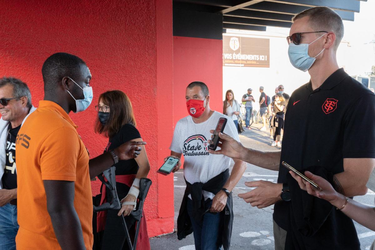 Un employé d'accueil vérifie les pass sanitaires de supporters du Stade Toulousain. Après une année de matches à huis-clos en raison de la crise sanitaire, le public a pu de nouveau se rendre au stade Ernest Wallon à l'occasion du match de clôture de la 2e journée du Top 14. Champion de France en titre, le Stade Toulousain recevait le Rugby Club Toulonnais. Le match s'est joué à guichets fermés et près de 19000 contrôles de pass sanitaires ont été effectués à l'entrée du stade. Le Stade Toulousain l'a remporté par 41 à 10. Toulouse, stade Ernest Wallon, le 12 septembre 2021.