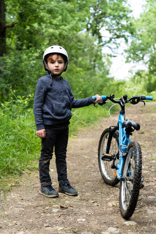 Un enfant pose à côté de son vélo sur un chemin de terre dans la forêt de Bouconne, à proximité de Toulouse, à l'issue du déconfinement. Toulouse - France - mai 2020.