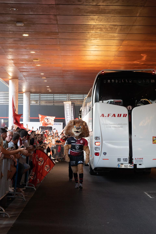 Ovalion, la mascotte du Stade Toulousain, détourne l'attention des spectateurs alors que le bus des joueurs toulonnais arrive au stade. Après une année de matches à huis-clos en raison de la crise sanitaire, le public a pu de nouveau se rendre au stade Ernest Wallon à l'occasion du match de clôture de la 2e journée du Top 14. Champion de France en titre, le Stade Toulousain recevait le Rugby Club Toulonnais. Le match s'est joué à guichets fermés et près de 19000 contrôles de pass sanitaires ont été effectués à l'entrée du stade. Le Stade Toulousain l'a remporté par 41 à 10. Toulouse, stade Ernest Wallon, le 12 septembre 2021.
