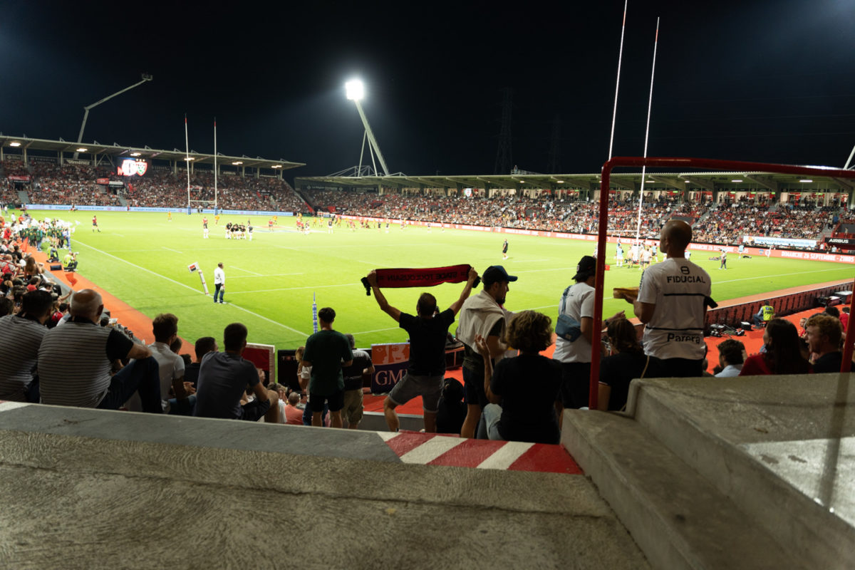 Un supporter du Stade Toulousain brandit une banderole alors que les équipes s'échauffent avant le coup d'envoi. Après une année de matches à huis-clos en raison de la crise sanitaire, le public a pu de nouveau se rendre au stade Ernest Wallon à l'occasion du match de clôture de la 2e journée du Top 14. Champion de France en titre, le Stade Toulousain recevait le Rugby Club Toulonnais. Le match s'est joué à guichets fermés et près de 19000 contrôles de pass sanitaires ont été effectués à l'entrée du stade. Le Stade Toulousain l'a remporté par 41 à 10. Toulouse, stade Ernest Wallon, le 12 septembre 2021.