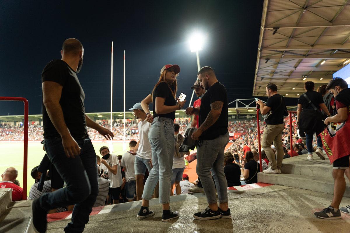 Des spectateurs viennent d'arriver dans le stade et s'apprêtent à rejoindre leur place dans les gradins. Après une année de matches à huis-clos en raison de la crise sanitaire, le public a pu de nouveau se rendre au stade Ernest Wallon à l'occasion du match de clôture de la 2e journée du Top 14. Champion de France en titre, le Stade Toulousain recevait le Rugby Club Toulonnais. Le match s'est joué à guichets fermés et près de 19000 contrôles de pass sanitaires ont été effectués à l'entrée du stade. Le Stade Toulousain l'a remporté par 41 à 10. Toulouse, stade Ernest Wallon, le 12 septembre 2021.