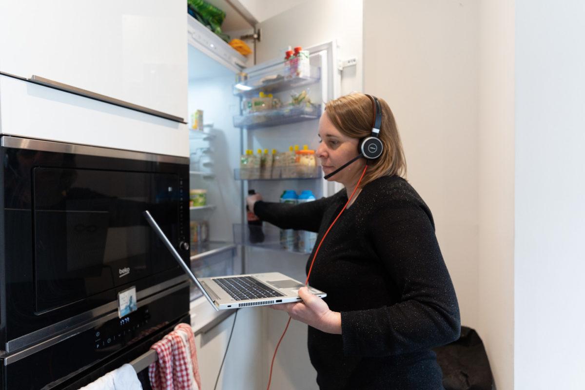 Son ordinateur à la main et son casque sur les oreilles, une employée en télétravail prend une boisson dans son réfrigérateur juste avant le début d'une vidéoconférence avec ses collègues. Toulouse, 26 novembre 2020.