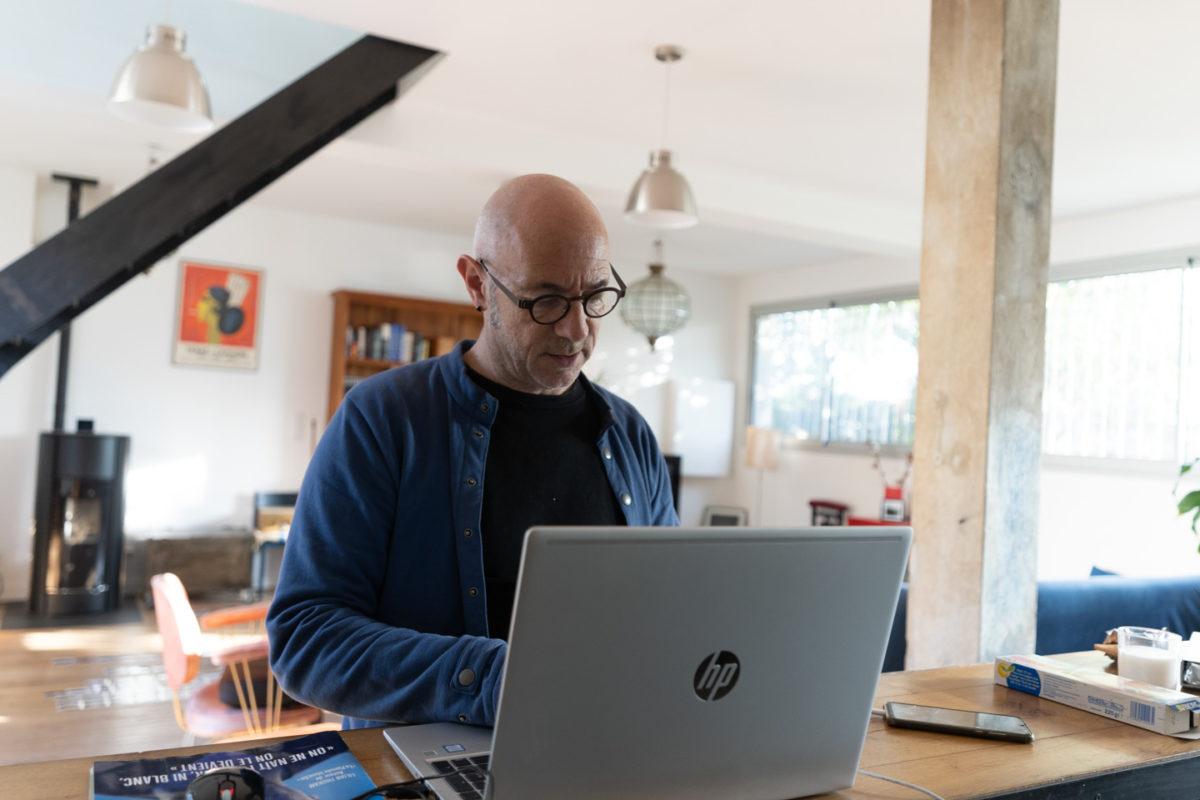 Un salarié en télétravail sur le bar de sa cuisine américaine. Toulouse, 27 novembre 2020.