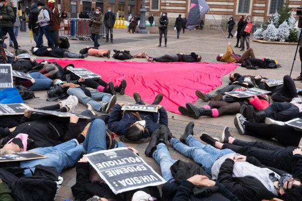 """Des militants d'Act Up s'allongent sur le sol pour un """"die in"""" autour du triangle rose étendu sur les pavés de la place du Capitole à l'occasion du rassemblement organisé par ActUp Sud-Ouest pour la journée mondiale contre le VIH/SIDA. Ils dénoncent notamment la politique sanitaire du gouvernement pendant la crise du Covid. Toulouse, le 1er décembre 2020."""